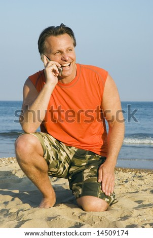 A happy laughing forties man is enjoying himself on a beautiful beach while having a conversation on his mobile phone. - stock photo