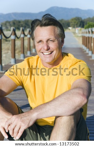 A happy laughing 44 year old man sitting on the boardwalk at the beach. - stock photo