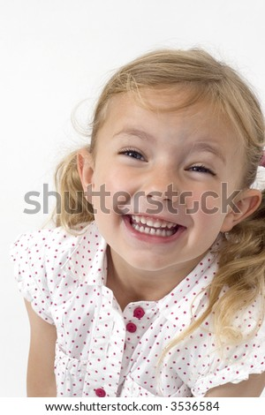A happy little girl in a spotty top - stock photo
