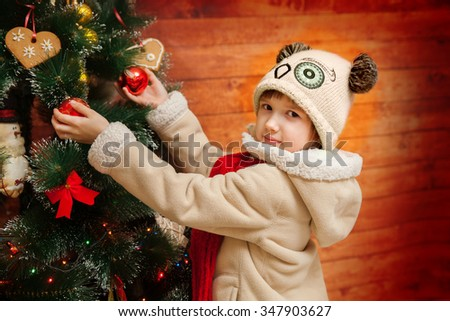 A happy little girl is decorating xmas tree - stock photo