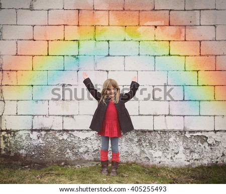 A happy little girl is standing against an old brick wall with a colorful rainbow and her hands are raised up for a fun weather outlook concept. - stock photo