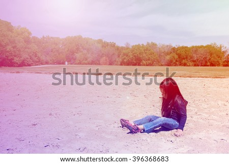 A happy little girl playing sand at public park with greenery background,filtered color tone in picture. - stock photo