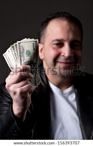 A happy man holds a handful of green American money with selective color. - stock photo