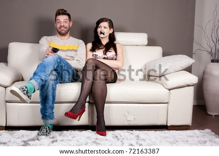 A happy man is watching TV in silence because he taped his girlfriend's mouth - stock photo