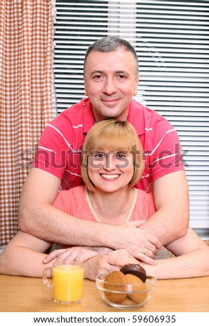 A happy middle-aged loving couple having cuddles during meal in the kitchen - stock photo