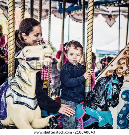 A happy mother and son are riding on a merry-go-round carousel together having fun at a fair or amusement park.  Filtered for a retro, vintage look.  - stock photo