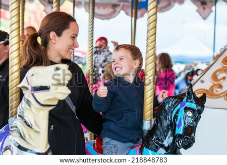 A happy mother and son are riding on a merry-go-round carousel together sharing a moment, smiling at one another having fun at a fair or amusement park.  The boy holds a thumbs up at the mother.  - stock photo