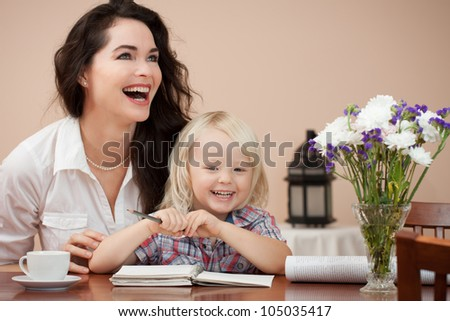 A happy mother and son sitting at table writing and drawing - stock photo