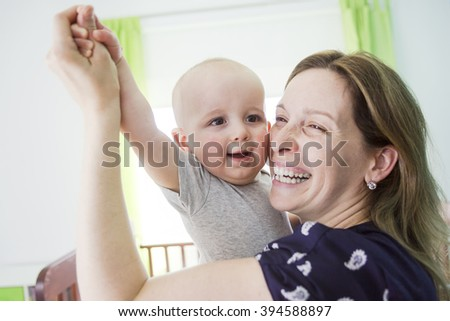 A Happy mother with her baby boy at home in bedroom - stock photo