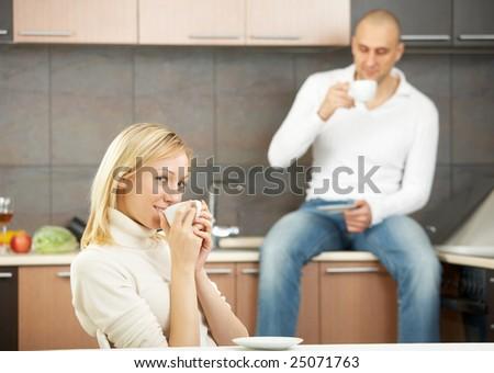 A happy pair drinks tea on a kitchen - stock photo