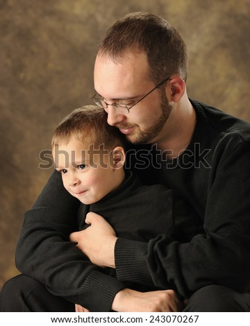 A happy preschool boy with his dad's arms wrapped snugly around him.   - stock photo