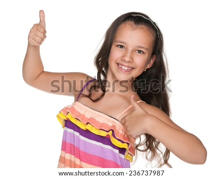 A happy preteen girl holds her thumbs up on the white background - stock photo