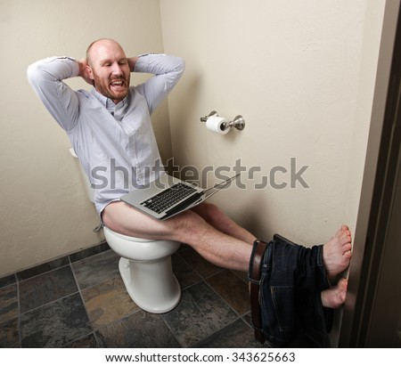 A happy relaxed man on his computer while on the toilet - stock photo