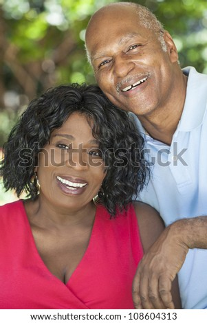 A happy senior African American man and woman couple in their sixties outside together smiling. - stock photo