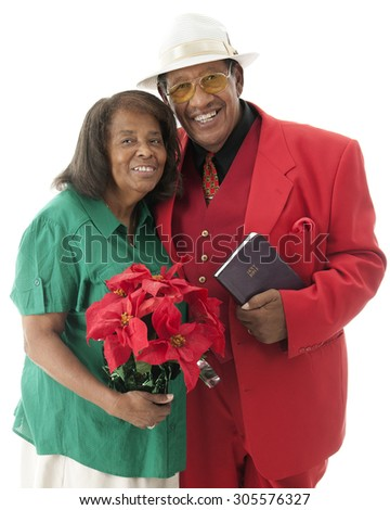 A happy senior couple dressed for Christmas.  She's carrying a pot of red poinsettias.  He's holding his Bible.  On a white background. - stock photo