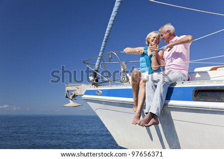 A happy senior couple holding hands, laughing while sitting on a sail boat on a calm blue sea - stock photo