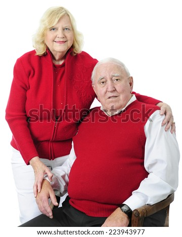 A happy senior couple in red sweaters.  On a white background. - stock photo