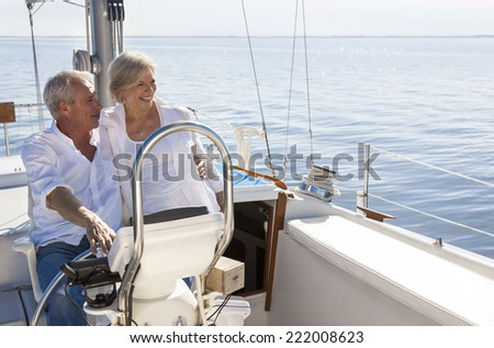 A happy senior couple sailing and sitting at the wheel of a sail boat on a calm blue sea - stock photo