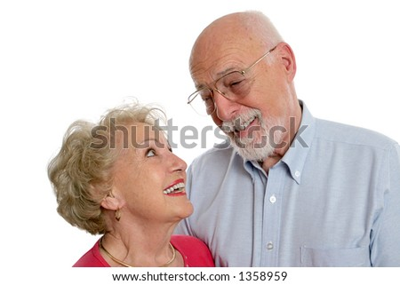 A happy senior couple sharing a private joke together.  She is wearing a hearing aid.  Isolated. - stock photo