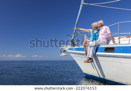 A happy senior couple sitting on the side of a sail boat on a calm blue sea looking and pointing to a clear horizon - stock photo