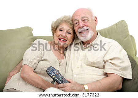 A happy senior couple watching television together. White background. - stock photo