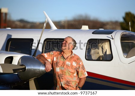 a happy, smart and well to do man stands proudly next to his latest airplane and looks to the sky to decide if he wants to fly to paris for French Fries - stock photo