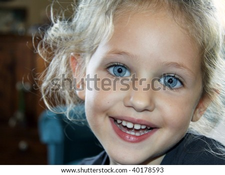 a happy smiling child portrait with blond hair and blue eyes - stock photo
