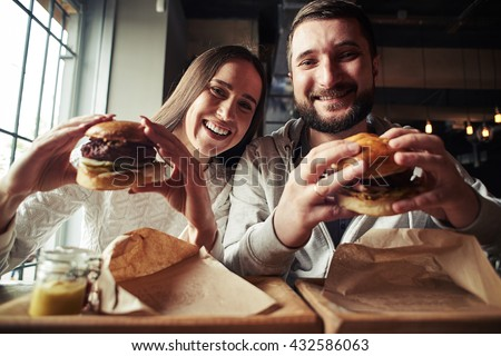 A happy smiling woman and a handsome bearded man are enjoying their delicious and tasty burgers in the burger-bar - stock photo