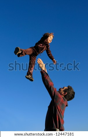 A happy two year old girl tossed into the blue sky by her father (portrait (vertical) orientation). - stock photo