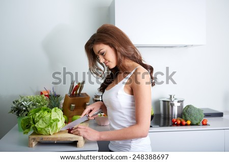 a happy woman cooking a meal in the kitchen. - stock photo