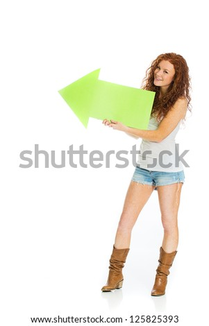A happy woman with a smile on her face holding an arrow pointing up and left. - stock photo