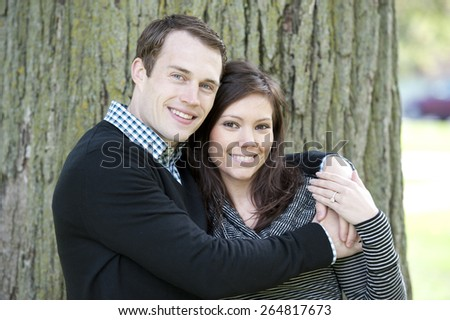 A happy, young and attractive couple looking at the camera on a sunny day at a park - stock photo