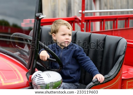 A happy young boy sits in an old shiny vintage red fire truck holding on to the steering wheel looking out.  - stock photo