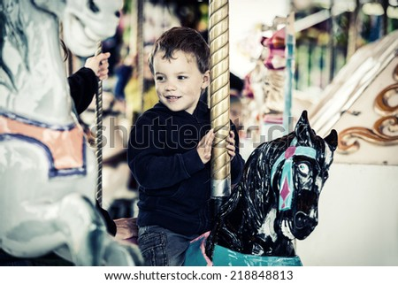 A happy young boy sits on a horse on a merry-go-round carousel ride at a fair or amusement park.  Filtered for a retro vintage look.  - stock photo