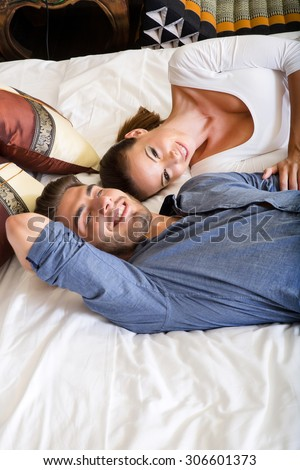 A happy young couple lying on the bed in a asian style hotel room.  - stock photo