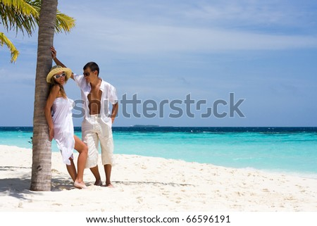 A happy young couple on a beach - stock photo