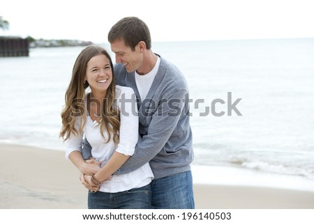 A happy young couple walking on the beach on a sunny day. - stock photo