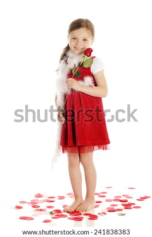 A happy young elementary girl holding a long-stemmed rose and surrounded by rose petals -- all in red and white.  On a white background. - stock photo