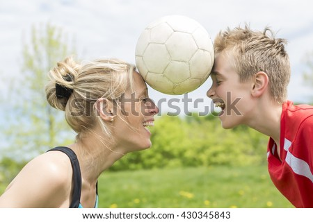 A happy young family playing football outdoor on a summer day - stock photo