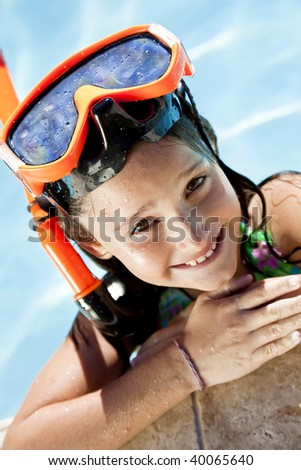 A happy young girl smiling and relaxing on the side of a swimming pool wearing orange goggles and snorkel - stock photo