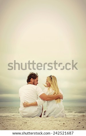 A happy young married couple in love is sitting on the white sand beach by the ocean, smiling at each other, with their arms around one another, on a cloudy morning.  Area for copy-space. - stock photo