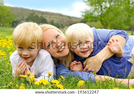 a happy young mother is laying outside hugging her two young children in a field of Dandelion flowers on a Spring day. - stock photo