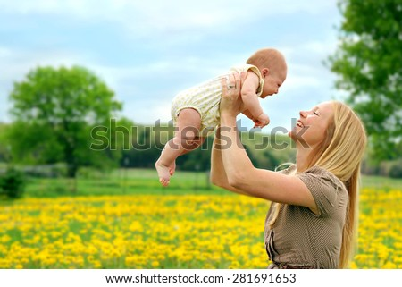 A happy young mother is smiling at her newborn baby girl as she lifts her up while  outside in the country - stock photo