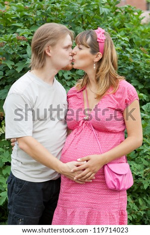a happy young pregnant woman with her husband kissing in a park - stock photo