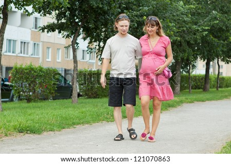 a happy young pregnant woman with her husband walking in a park - stock photo