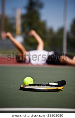 A happy young tennis player lying down on the court after winning - stock photo