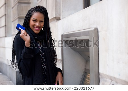 a happy young woman holding a cash card at a cash mashine. - stock photo