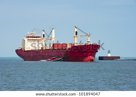 A harbor tugboat helps a large ocean going freighter turn left around a navigation beacon at the entrance to harbor at the Port of Cleveland, Ohio from Lake Erie - stock photo