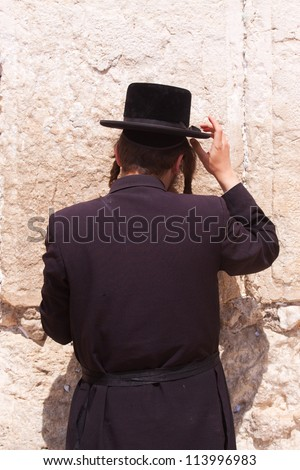 A Haredi Jew praying in front of the Western Wall in Jerusalem, Israel - stock photo