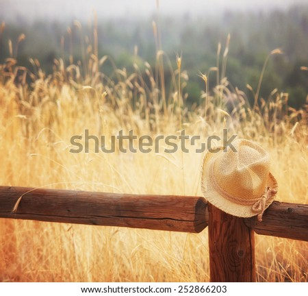 a hat on a fence during sunset or sunrise toned with an instagram like filter  - stock photo